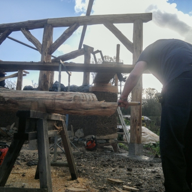 LandWorks trainee chiselling the join on the end. Timber frame land art sculpture