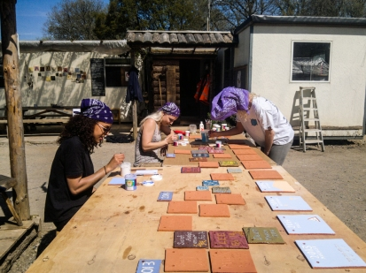 Plymouth University art students Hannah, Paige, and Megan painting ceramic clay tiles